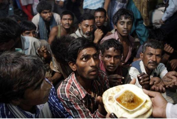 Những người đàn ông vô gia cư người Ấn Độ đang chờ đợi để nhận thức ăn miễn phí được phân phối bên ngoài một nhà thờ Hồi giáo của Eid al-Fitr ở New Delhi, Ấn Độ