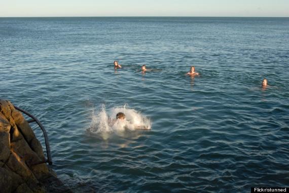 Những người đàn ông khỏa thân bơi lội dưới nước biển lạnh