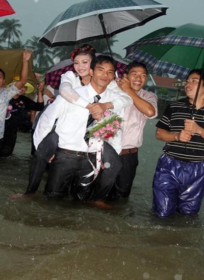 Cơn mưa nặng hạt trên đầu trong khi nước dâng ngập đến gối vẫn không làm sờn lòng chú rể Hưng, một lính hải quân tại Cam Ranh, Khánh Hòa, bên cạnh cô dâu của mình.