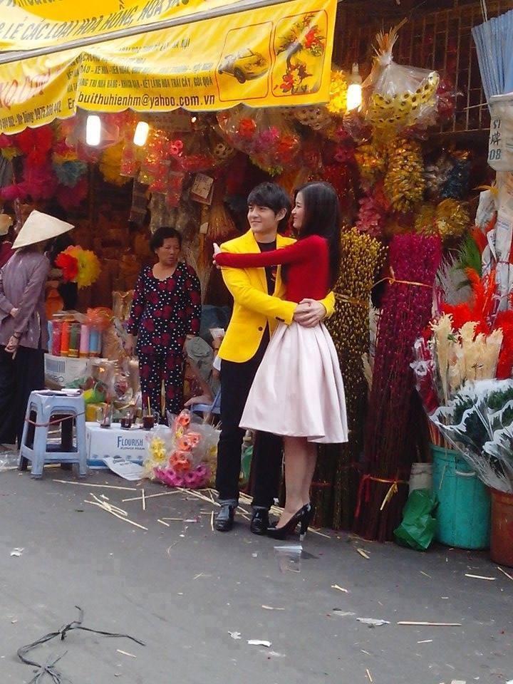 """Bella - """"Thị Mẹt hếch hi"""" - đáng yêu của Quỳnh Anh   Ông Cao Thắng - Đông Nhi """"nổi bần bật"""" trong sắc vàng - đỏ giữa chợ hoa. Cả hai thực hiện bộ ảnh mừng xuân và không ngần ngại thể hiện tình cảm cùng nhau."""