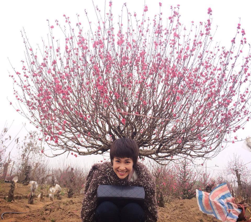"""Uyên Linh hiện đang ở ngoài Bắc, cô nàng dí dỏm tạo kiểu cùng hoa đào và chú thích: """"Hoa nở trên đầu"""" khiến fan của cô vô cùng thích thú."""