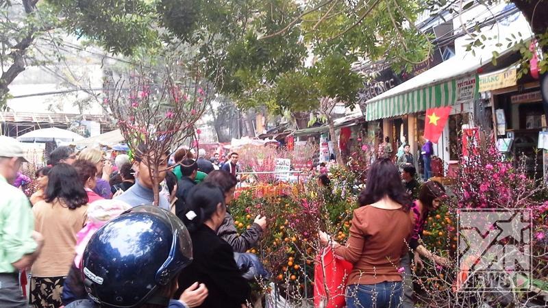 Dòng người đông chen chúc nhau trong chợ hoa Tết nhằm mong mua được một loại hoa vừa ý cho gia đình mình.