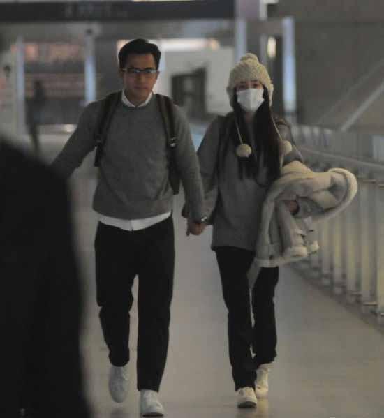 Cặp đôi nắm chặt tay nhau khi đi tới sân bay.