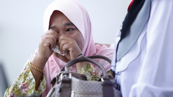 Một thân nhân của hành khách trên chuyến bay mất tích khóc nức nở khi mỏi mòn chờ đợi tin tức - Ảnh: Reuters