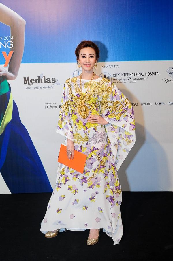 """Khác với một dàn mỹ nhân xúng xính váy áo đến dự show """"Biển nhớ"""" của Đỗ Mạnh Cường, """"Nữ hoàng khiêu vũ"""" Ngân Khánh lại chọn cho mình một bộ đồ hiệu phủ từ đầu đến chân là những mẫu mới nhất của Versace."""