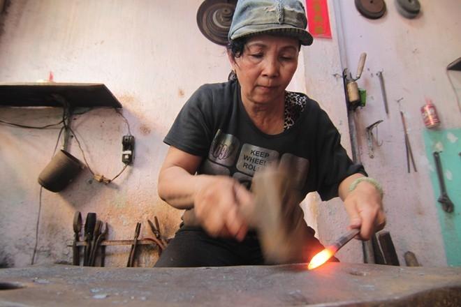 """Đến bây giờ, nghề thợ rèn vẫn là nguồn thu nhập chính của gia đình. Vợ chồng bà có 2 người con nhưng công việc vẫn chưa ổn định, ông bà cố làm tăng thu nhập để lo cho con cái. """"Bây giờ người ta làm bằng máy hết, ít ai rèn thủ công nữa. Tôi và ông xã cứ làm được ngày nào hay ngày ấy, lai rai kiếm sống qua ngày"""", bà Nguyệt chia sẻ."""