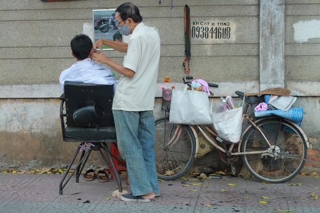 Sài Gòn ngày càng nhiều tiệm hớt tóc sang trọng thì những tiệm cắt tóc vỉa hè càng thưa thớt dần. Trên những con đường lớn, hầu như đã vắng hẳn dịch vụ này. Trong ảnh, một tiệm cắt tóc trên đường Tôn Đức Thắng (Q.1).