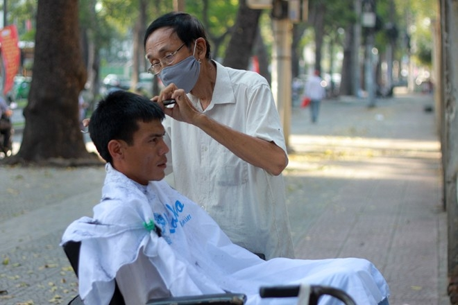 """Khách hàng của ông Tuấn chủ yếu là tầng lớp lao động bình dân, người lớn tuổi. """"Nhiều người vẫn thích hớt tóc vỉa hè vì sự gần gũi, thoải mái. Khách và thợ có thể bàn đủ thứ chuyện với hằng ngày mà không thấy chán"""", ông Tuấn chia sẻ."""