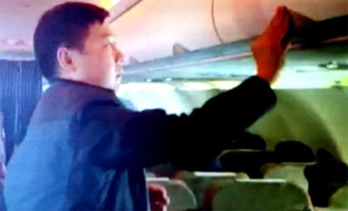 Hình ảnh hành khách Zhang Giang (Trung Quốc) ăn cắp đồ tại giá hành lý trên chuyến bay VN 600 Bangkok (Thái Lan) - TP HCM chiều 19-1 cũng đã bị tiếp viên Vietnam Airlines bắt quả tang và quay clip làm bằng chứng