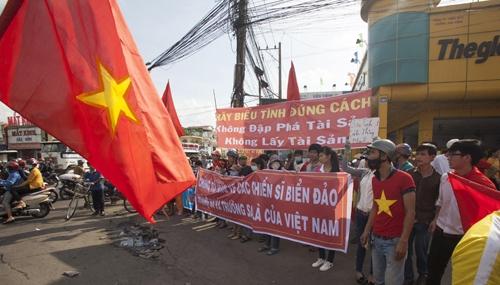 Người dân cầm biểu ngữ kêu gọi biểu tình đúng cách sau vụ bạo loạn ở Bình Dương. Ảnh: Reuters