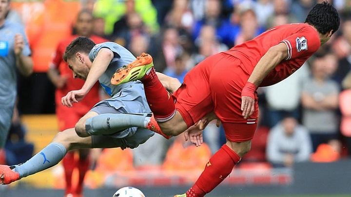 Pha va chạm với Dummett (giữa) khiến Suarez dính chấn thương.