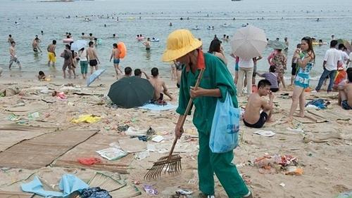 Một công nhân vệ sinh dọn dẹp rác thải xung quanh người đi tắm biển. Ảnh: Splash News Australia.
