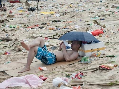 Một thanh niên hôm 3/6 thoải mái đọc sách giữa đống rác gồm vỏ chai lọ, túi ni lông... Ảnh: Splash News Australia.