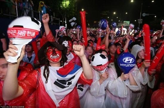 Hàng ngàn người hâm mộ Hàn Quốc đội mưa tới sân vận động Seoul để cùng xem tường thuật trực tiếp trận đấu giữa Hàn Quốc và Nigeria.