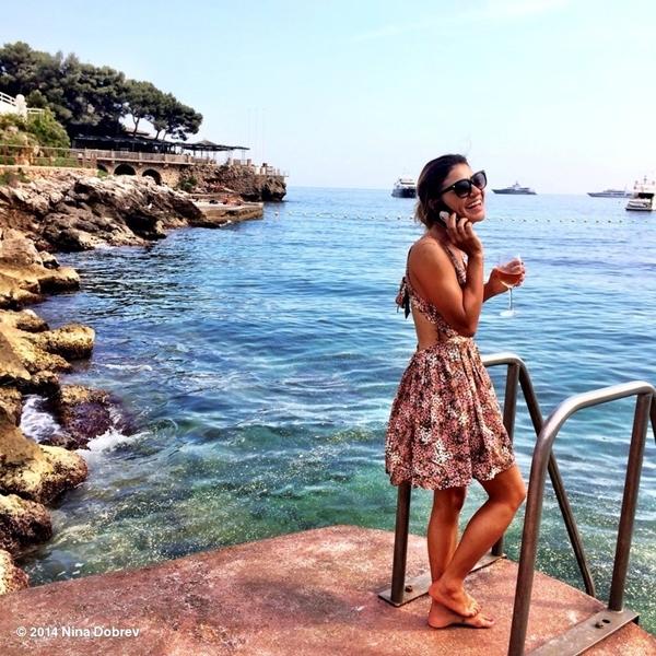 Nina Dobrevtận hưởng ly rượu vang bên cạnh bờ biển tuyệt đẹp.