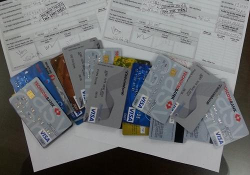 Giấy biên nhận nạn nhân nộp tiền và những chiếc thẻ được chúng rút tiền của các bị hại.