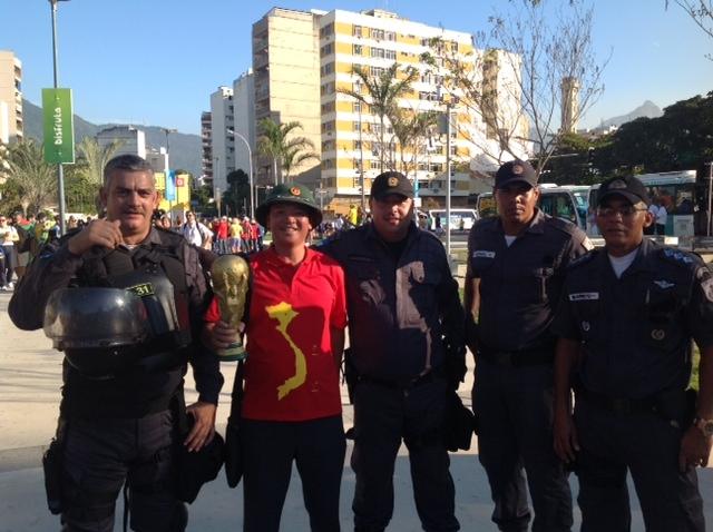 ... cùng với chiếc mũ cối quen thuộc khi chụp ảnh lưu niệm với cảnh sát Brazil