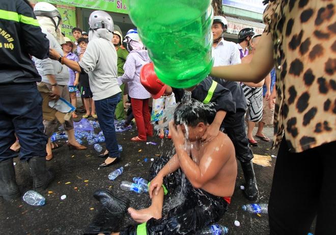 Nhiều người cởi bỏ quần áo, ngồi bệt xuống đường và được người dân xối nước sạch lên người, dùng mọi vật dụng để quạt mát.