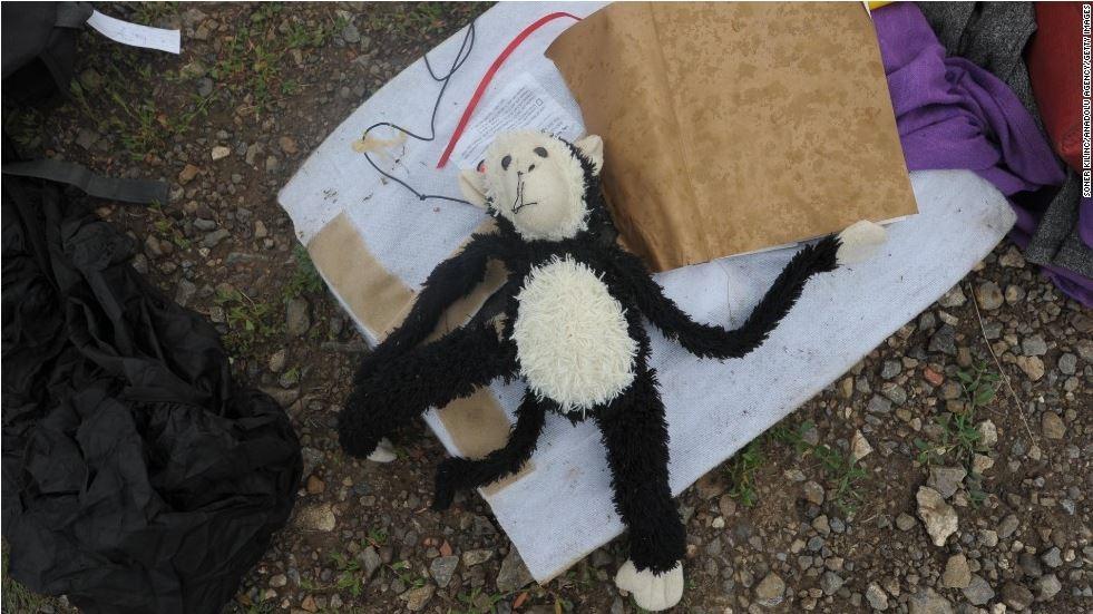 Một chú khỉ bông nằm chỏng chơ giữa đống đổ nát