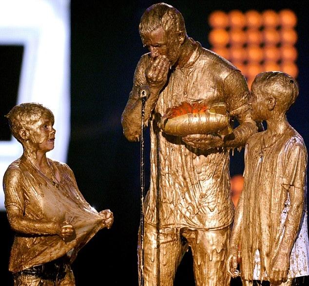 [Bóng Đá] Bố con Beckham tắm sơn vàng bất đắc dĩ