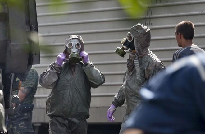 Những người vận chuyển thi thể phải mặc đồ bảo hộ và đeo mặt nạ khi đưa nạn nhân vào túi đen và chuyển lên xe tải. Ảnh: AP