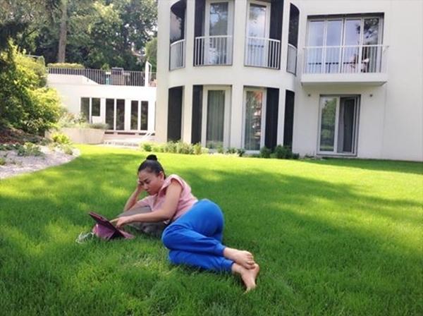 """Thu Minh mang theo cả gối """"nằm ườn"""" chơi máy tính bảng trong khu vườn xanh mát ở nhà. Những hình ảnh giản dị này góp phần không nhỏ mang hình ảnh của cô đến gần với người hâm mộ hơn."""