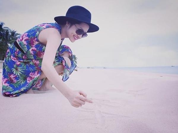 Bảo Anh diện váy in họa tiết hoa duyên dáng khi thả bộ trên bờ biển. Cô nàng còn nghịch ngợm viết tên mình lên cát để làm kỉ niệm.