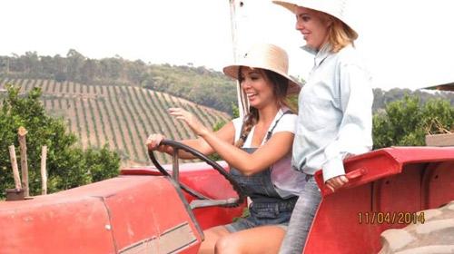 Hai cô gái trẻ lái máy cày trong thị trấn