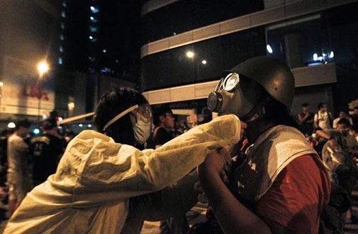 Người biểu tình sửa sang mặt nạ và mũ bảo hiểm cho nhau để đối phó với hơi cay từ cảnh sát tại quận Mongkok. Vũ khí họ mang theo trong cuộc chiến dân chủ này là những vật dụng rất đơn sơ trong gia đình áo mưa, bao nilon, kính mắt, khẩu trang y tế... Ảnh: Reuters.
