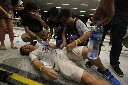 Một sinh viên lả đi và được bạn bè sơ cứu sau khi hít phải hơi cay của cảnh sát. Ảnh: Reuters.