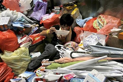 Một sinh viên trẻ ngồi co quắp giữa một đống đồ dùng và ăn vội hộp cơm sau nhiều giờ biểu tình trên đường phố. Ảnh: AP.