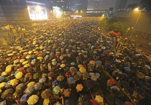 Cơn mưa nặng hạt vào đêm qua không thể ngăn cản tinh thần đấu tranh của hàng chục nghìn người biểu tình trên đường phố Hong Kong. Những chiếc ô họ dùng để che hơi cay từ cảnh sát là vật dụng hữu hiệu vào những ngày nắng mưa bất chợt như thế này. Chiếc ô đã trở thành biểu tượng của Occupy Central. Ảnh: AP