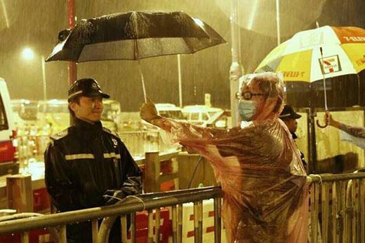 Trong cơn mưa, cảnh sát và người biểu tình dường như xích lại gần nhau hơn. Ảnh: News Hong Kong.