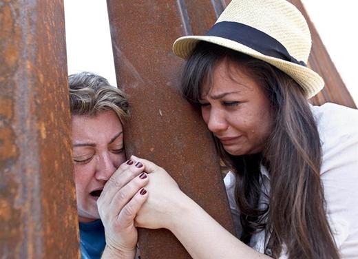 Gorete Borges Teodoro và con gái của cô, Renada Teodoro đang nắm tay nhau ngay tại hàng rào biên giới Nogales, Arizona vào năm 2013. Sáu năm trước, Gorete đã phải rời xa gia đình vì bị trục xuất sang Mexico.