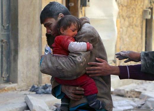 Một cậu bé đang ôm chặt em gái của mình sau khi cứu cô bé khỏi căn nhà bị đổ nát của họ tại Syria