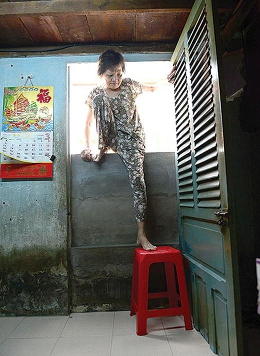Họ ra vào nhà bằng cách chui, bò, bắc thang, kê ghế nhựa bên trong. Bà Nguyễn Thị Hoài đặt ghế nhựa ngay cửa để lên xuống nhưng vẫn rất thấp so với mặt đường