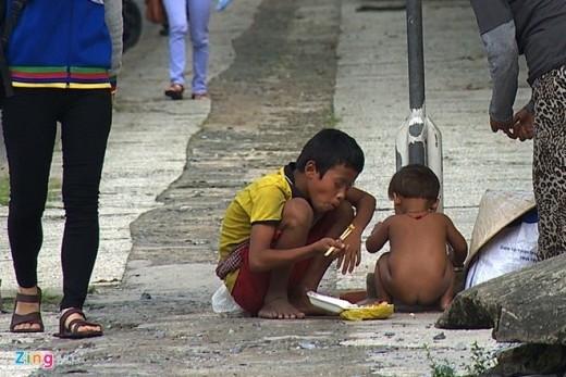 Sau một buổi sáng, những đứa trẻ ăn trưa với cơm hộp và chơi chốc lát ngay bên lề đường.
