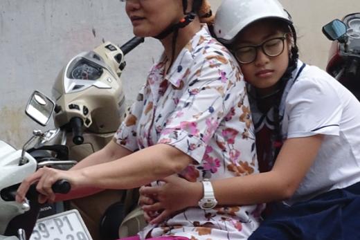 Ngủ gục sau lưng mẹ trên đường đến trường không còn là hình ảnh xa lạ - Ảnh: Phùng Huy
