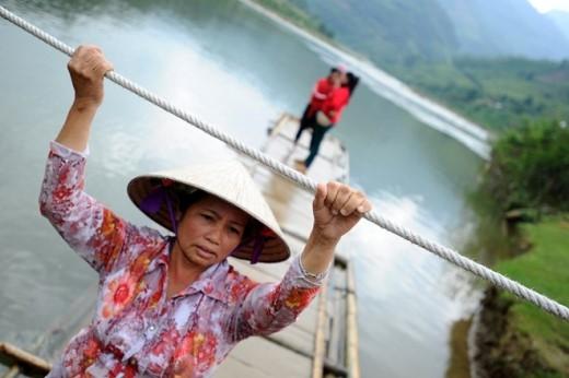 """Chị Vũ Thị Đào, đã 27 năm làm nghề đưa người qua suối kể: """"Có khi nửa đêm phải dậy để đưa người đi bệnh viện. Còn những hôm nước lũ cao chị phải để 2 người con trai có sức khỏe kéo thay""""."""