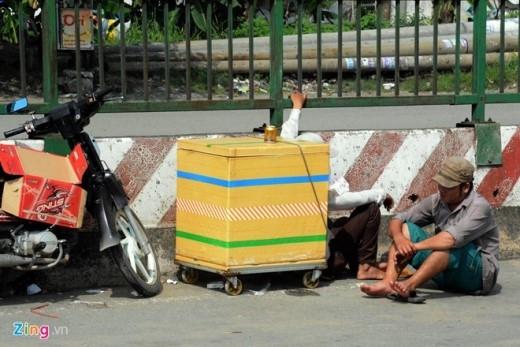 Một đôi vợ chồng ngồi chờ khách ngay giữa đường cùng với đồ nghề buôn bán.