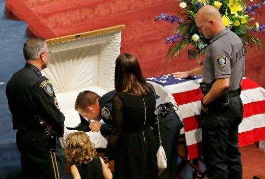 Trong lễ tang ngày 28-8-2014, người bạn của chú chó K-9 Kye là sĩ quan cảnh sát Ryan Stark, cúi sát quan tài để tạm biệt Kye lần cuối. Hơn 1.000 người đưa tiễn Kye trong một tang lễ trọng thể sau khi nó hi sinh vì nhiệm vụ. Kye là chó nghiệp vụ của sở cảnh sát thành phố Oklahoma (Mỹ) và bị đâm chết bởi một nghi phạm trộm cắp xe hơi - Ảnh: SUE OGROCKI-AP