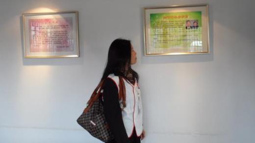 Cô Zhou Songying đứng trước di ảnh của cha mẹ tại nhà tưởng niệm.
