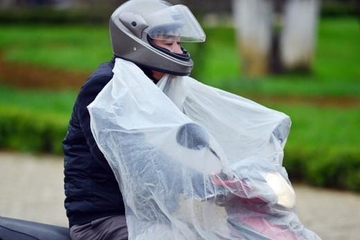 Một số người đi xe máy phải khoác thêm áo mưa để chống lạnh.