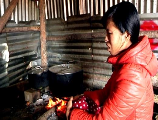 Chị Phan Thị Hoa vợ anh Trương Tuấn Việt ngồi nấu cháo cho chồng và các nạn nhân. Ảnh: Phạm Duy
