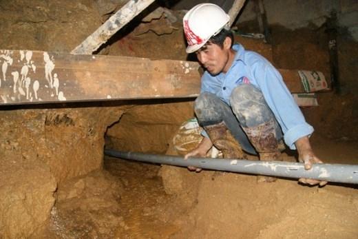 Mũi khoan này rộng khoảng 7cm, dài 60m, vị trí khoan cách nền hầm 50cm. Chiều 20/12, nước từ khoang hầm các công nhân mắc kẹt xối mạnh ra ngoài. Trong ảnh: các công nhân đang lắp đạt đường ống nhựa (có khoan các lỗ nhỏ quanh ống để thu nước) để dẫn nước ra ngoài, đề phòng nước tiếp tục làm xói lở đất.