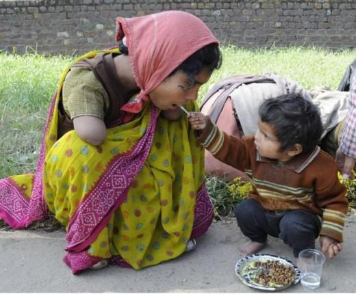 Em bé 2 tuổi bón thức ăn cho người mẹ tàn tật