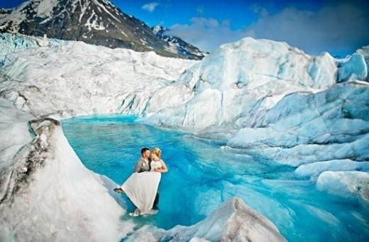 """Theo Viralspell, cặp đôi người Mỹ đã cùng nhiếp ảnh gia Josh Martinez đi trực thăng đến dòng sông băng Alaska để thực hiện bộ ảnh tuyệt đẹp. Tuy phải chịu đựng khí hậu lạnh lẽo và địa hình nguy hiểm, hai vợ chồng vẫn rất vui vẻ, phối hợp nhiệt tình và hết sức ăn ý khi tạo dáng. Được biết, họ cũng là những người """"tiên phong"""" đến sông băng Alaska chụp ảnh cưới."""
