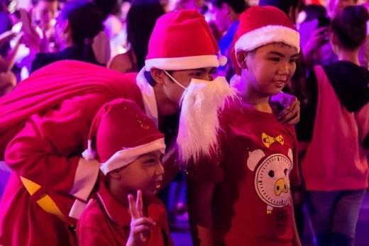 Trẻ em thích thú các 'ông già Noel' với bộ râu trắng. Ảnh: Hải An.