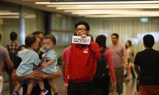 Nhân viên sân bay Changi cầm tấm biển chỉ dẫn thân nhân của các hành khách trên chuyến bay số hiệu QZ8501 của hãng hàng không AirAsia. Ảnh: Reuters