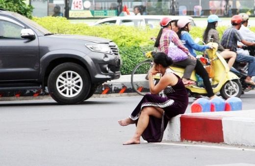 Quậy chán chê, người đàn bà ngồi trầm ngâm trên dải phân cách giữa đường.